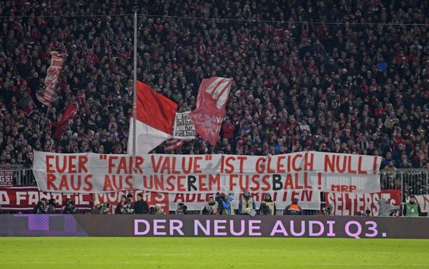 """""""Bayern Fans halten Banner hoch, mit der Aufschrift: """"""""Euer """"""""Fair Value"""""""" ist gleich null! Raus aus unserem Fussball!"""""""""""""""