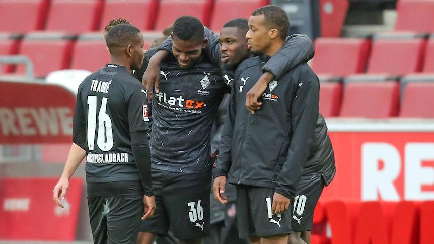 Gladbacher Spieler umarmen sich nach dem Bundesliga-Sieg in Köln.