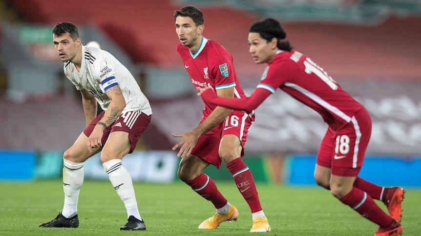 Die Fußballprofis Marko Grujic (Mitte) und Granit Xhaka (l.) blicken während eines Spiels gespannt auf den Ball.