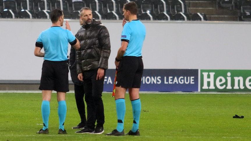 Marco Rose (M.), Trainer der Gladbacher Borussia, nach der 2:3-Niederlage am Dienstagabend in der Champions League gegen Inter Mailand, im Austausch mit den niederländischen Unparteiischen.