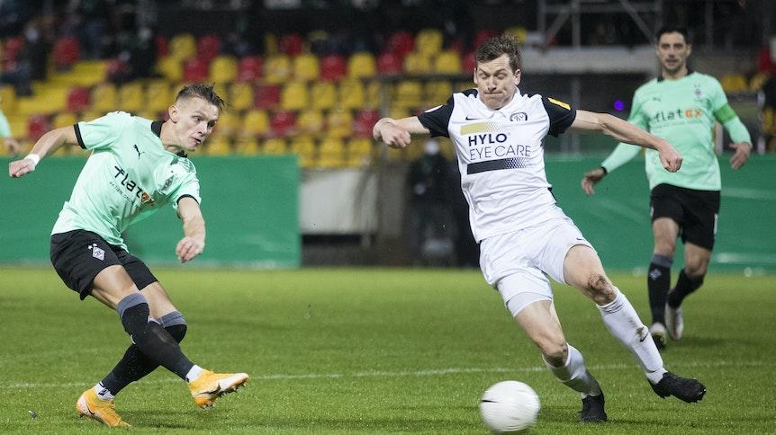Gladbachs Hannes Wolf (l) macht das Tor zum 0:1 gegen Elversbergs Lukas Kohler (M).
