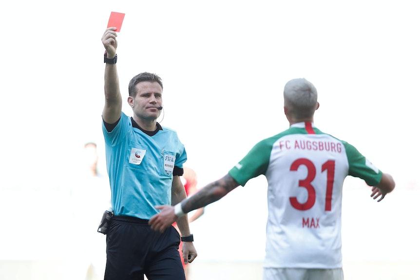Schiedsrichter Brych zeigt Augsburgs Max die Rote Karte - und nimmt diese Minuten später wieder zurück.