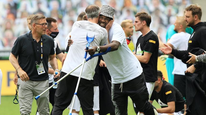 Marcus Thuram (M.) wird von Marco Rose nach dem feststehenden Champions-League-Einzug nach dem Spiel gegen Hertha BSC umarmt.