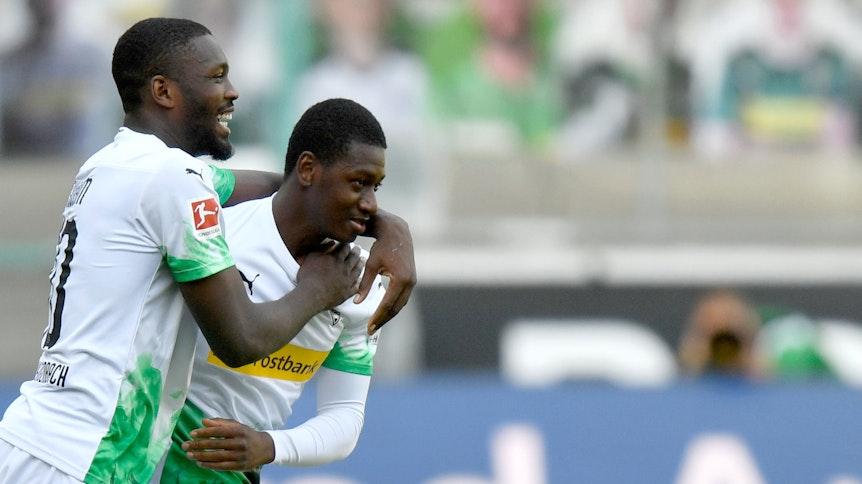 Marcus Thuram feiert Mamadou Doucouré bei dessen Debüt für Borussia Mönchengladbach.