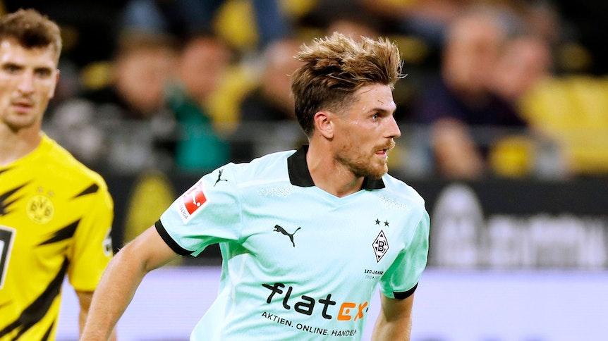 Jonas Hofmann, Spieler der Gladbacher Borussia, kontrolliert den Ball, sein Blick ist auf das Spielfeld gerichtet.