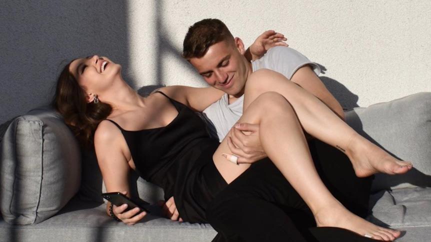 Jordan Beyer und Freundin Julietta Malina posieren auf dem Sofa.