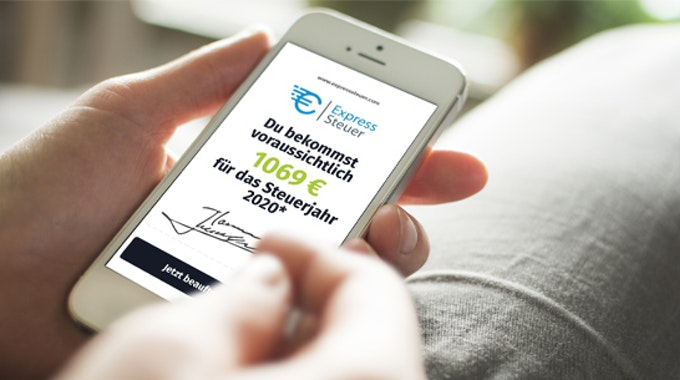 Ein Mann macht seine Steuererklärung über den Online-Steuer-Service ExpressSteuer am Smartphone.