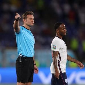 Schiedsrichter Felix Brych gestikuliert hinter Raheem Sterling bei der EM 2021.