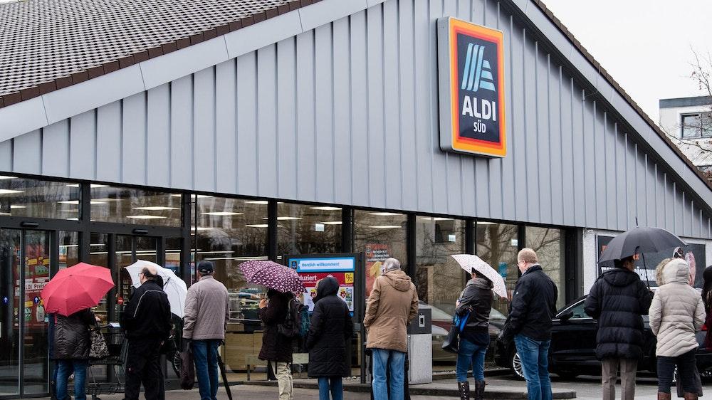 Kunden warten vor einer Aldi-Süd-Filiale. Der Hersteller des Aldi-Waschmittels Tandil hat Insolvenz angemeldet.