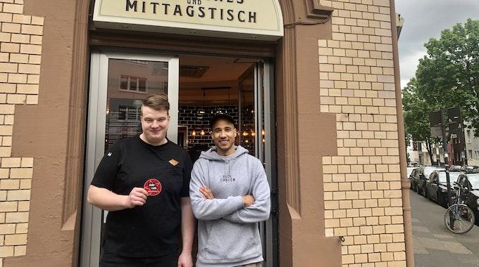 Moritz Issinger und Saloum Doucouré stehen vor dem Eingang ihres Delis in der Kölner Südstadt.