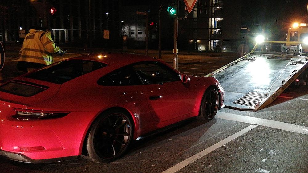 Ein Abschlepper hat einen roten Porsche am Haken.