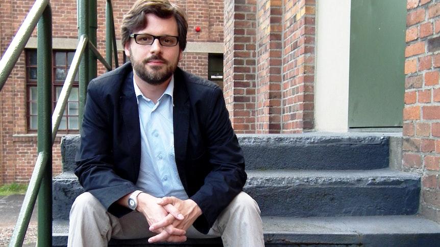 Sebastian Bartoschek (38) sitzt auf einer Treppenstufe.