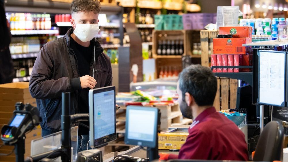 Ein junger Mann trägt bei seinem Einkauf in einem Supermarkt einen Mundschutz, der Verkäufer sitzt hinter einer Plexiglasscheibe. Edeka hat in einigen Filialen nun spezielle eBons an den Kassen eingeführt.