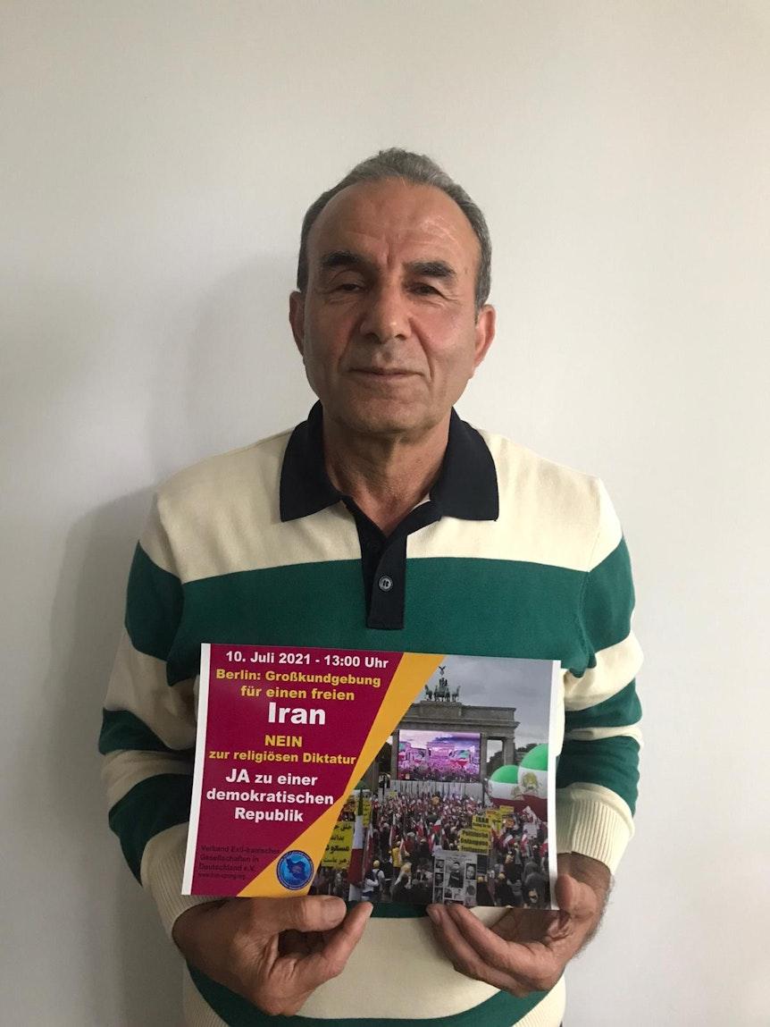 Der Kölner Taxi-Fahrer Ali Sajadi hält ein Plakat mit Bezug auf die Demo gegen den iranischen Präsidenten Ebrahim Raisi am 10. Juli in Berlin.