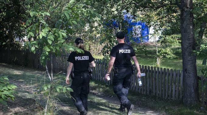 Zwei Polizisten sind in einer Kleingartenanlage unterwegs.