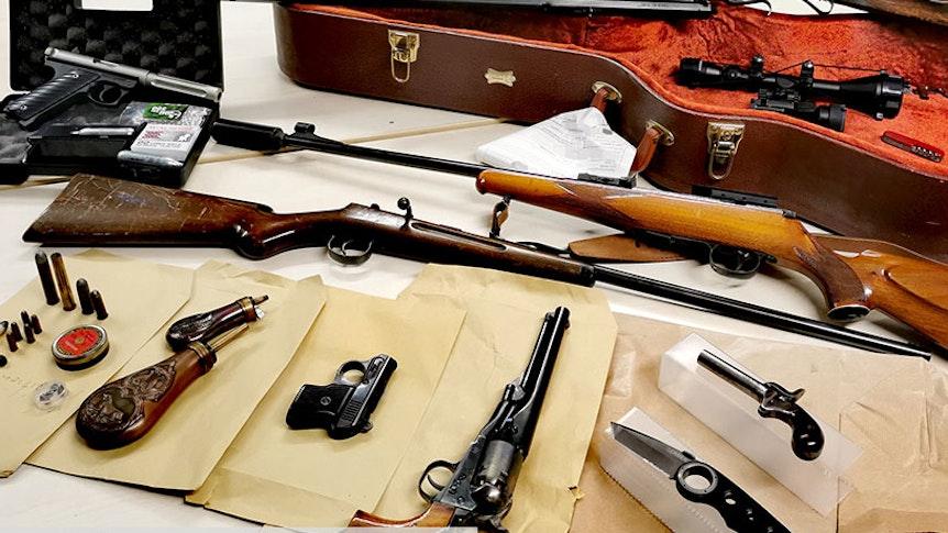 Auf einem Tisch liegen sichergestellte Gewehre, Pistolen, Messer und Munition.