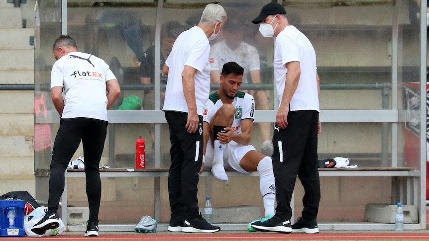 Gladbach-Verteidiger Ramy Bensebaini sitzt auf der Auswechselbank, die Physios schauen sich seinen Fuß beim Testspiel gegen Viktoria Köln am 10. Juli 2021 im Grenzlandstadion an.