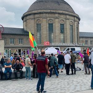 Demo-Teilnehmer stehen in Köln-Deutz mit Flaggen vor dem Bahnhof.