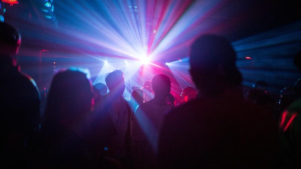 Menschen feiern in dem Symbolbild in einer Disco, Silhouetten sind im Laser-Licht zu sehen. Eine Reiserückkehrerin aus Mallorca sorgte in einem Club in Karlsruhe für einen Corona-Ausbruch.