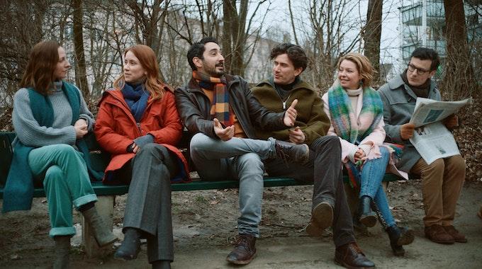"""Eko Fresh und weitere Schauspieler der neuen Serie """"Das Streben nach Glück"""" sitzen bei Dreharbeiten zusammen auf einer Bank."""