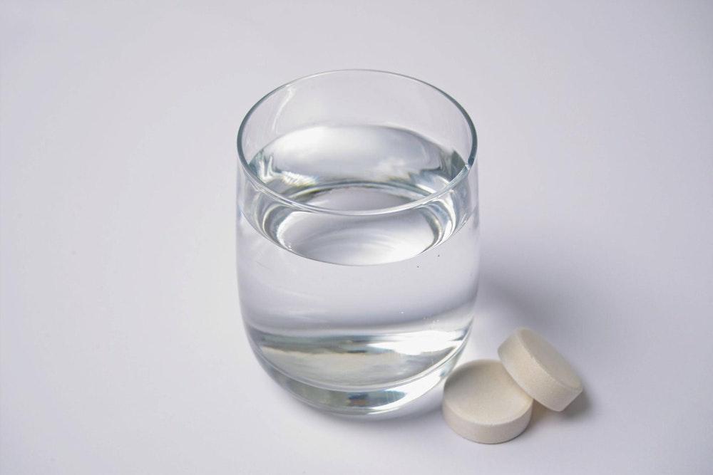 Das Symbolbild zeigt ein Wasserglas mit zwei Tabletten, die daneben liegen. Der Hersteller Abtei ruft bestimmte Vitamin-Präparate zurück, die bundesweit verkauft wurden.