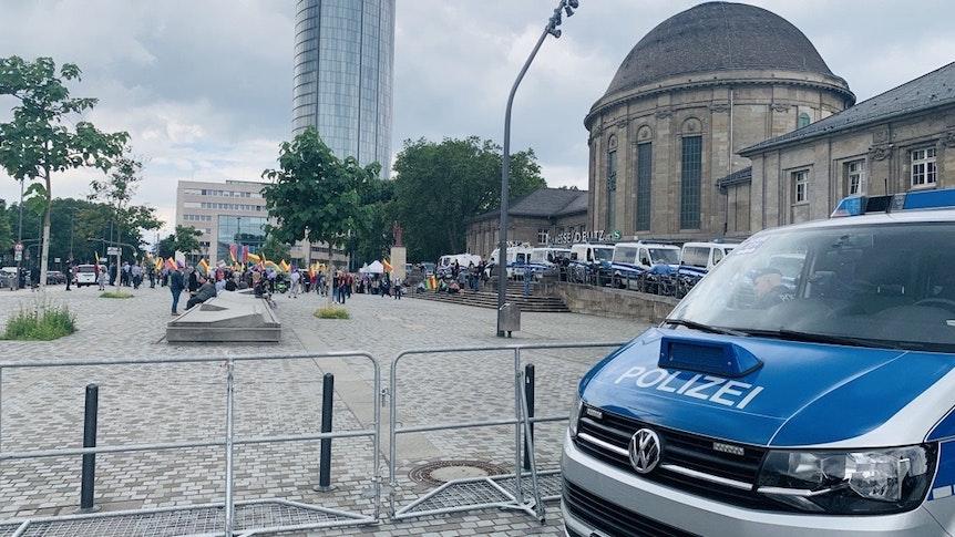 Ein Wagen der Kölner Polizei steht vor dem Deutzer Bahnhof. Im Hintergrund sind Demonstrierende zu sehen.