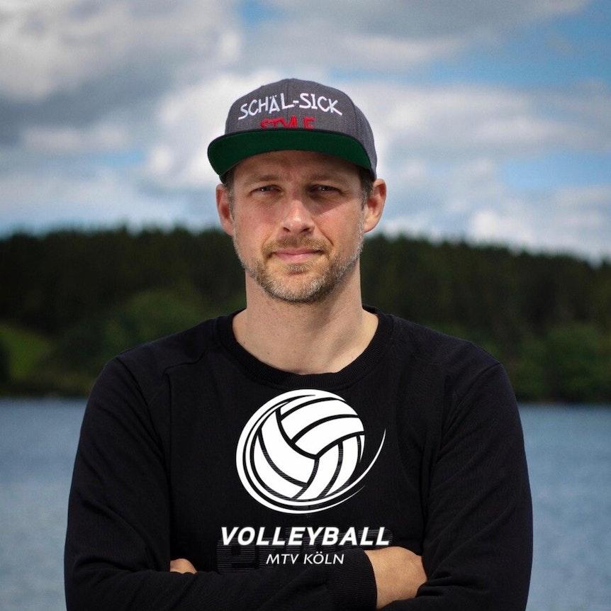 Der Kölner Kai Vogel steht mit einem Volleyball-Pullover vor dem Rhein.