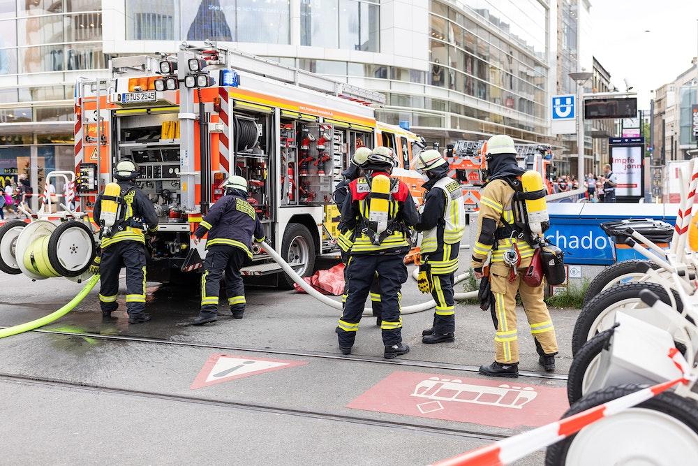 Einsatzkräfte der Feuerwehr stehen vor dem U-Bahnhof Schadowstraße.