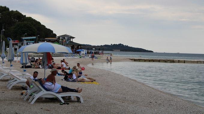 Urlauber lieben am Strand von Fazana auf der kroatischen Halbinsel Istrien.