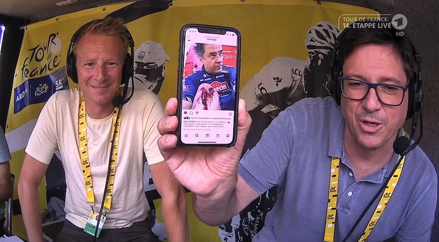 ARD-Kommentator Florian Naß und Ex-Profi Fabian Wegmann zeigen während der Übertragung der 14. Tour-Etappe einen Instagram-Post von Jan Josef Liefers