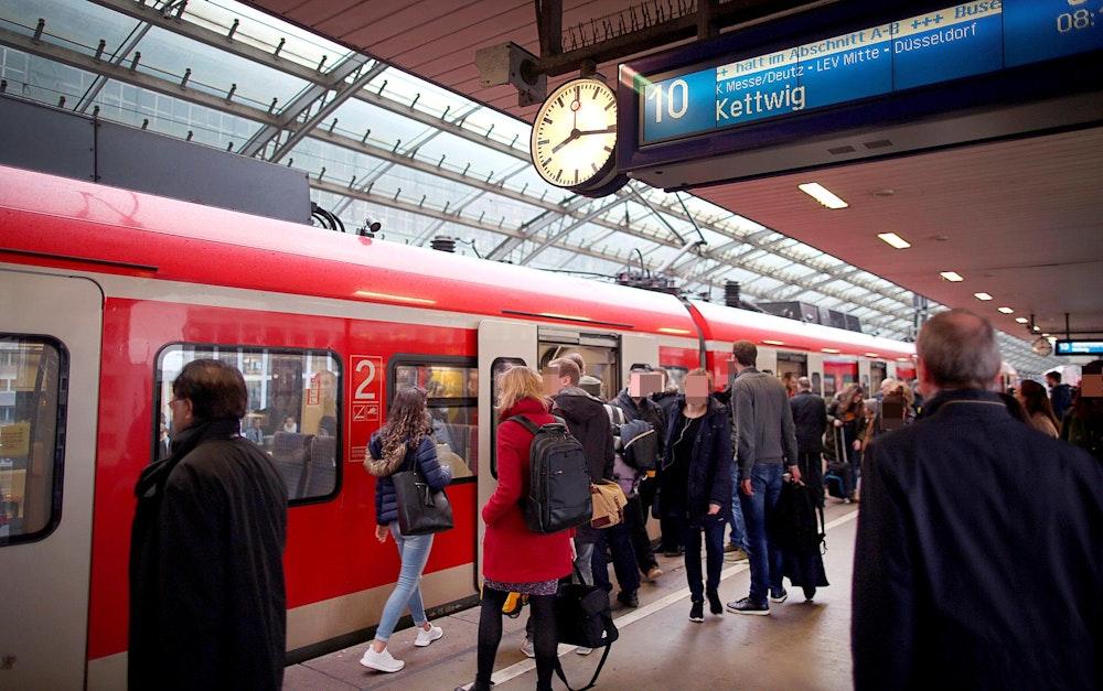 Fahrgäste an einem Zug im Kölner Hauptbahnhof.