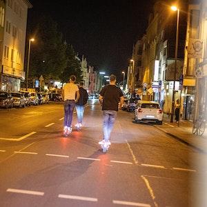 Drei junge Männer fahren mit E-Scootern in Köln-Sülz.