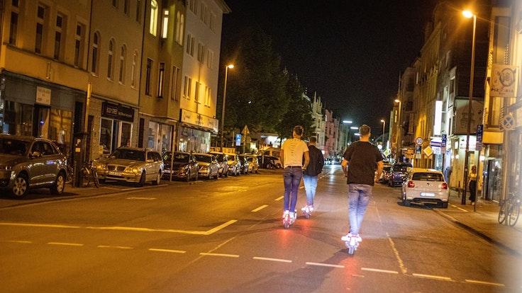 Junge Männer fahren in der Nacht auf E-Scootern auf der Berrenrather Straße in Köln-Sülz.