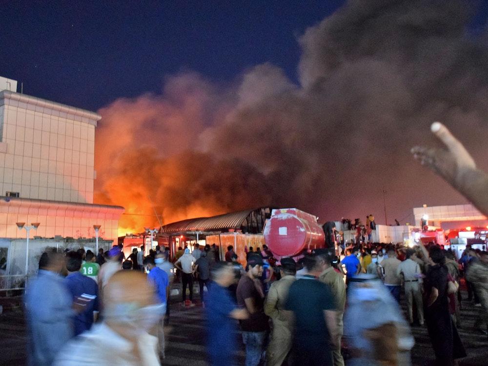 Menschen stehen in der Umgebung des Krankenhauses, aus dem große Flammen und Rauch aufsteigen.