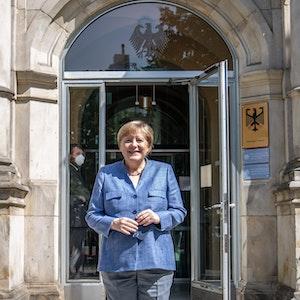 Bundeskanzlerin Angela Merkel (CDU) steht am Eingang des Robert Koch Instituts (RKI).