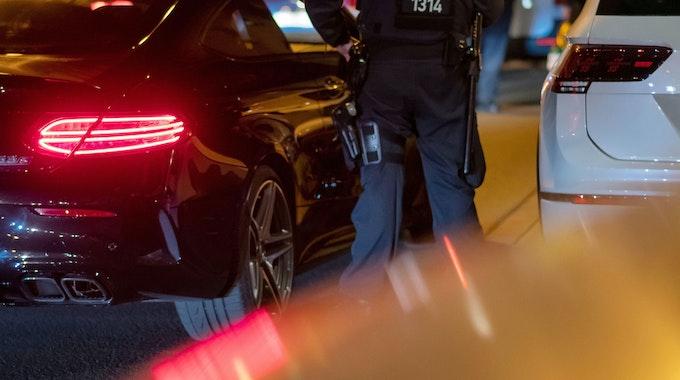 Ein Polizist steht an einem Pkw.