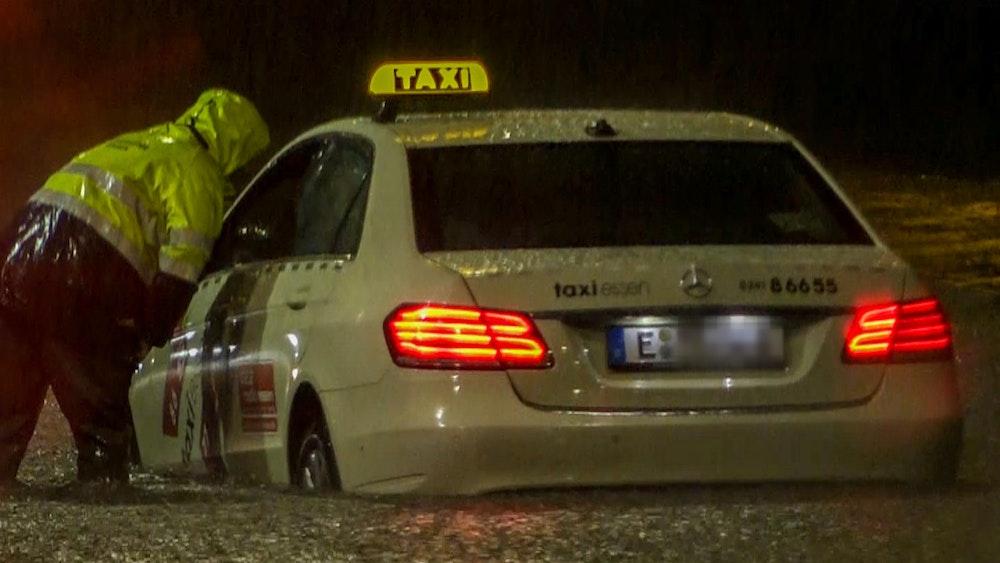 Ein Feuerwehrmann spricht mit dem Fahrer eines Taxis, das sich im Hochwasser festgefahren hat. Starkregen lässt Straßen überfluten.
