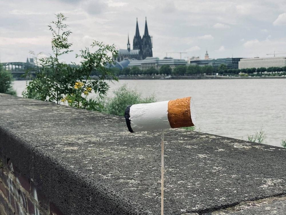 Eine überdimensionale Zigarettenkippe ist auf einer Mauer am Kölner Rheinufer befestigt, im Hintergrund der Dom.
