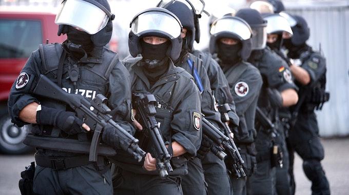 Zehn SEK-Beamte stehen mit Helmen, Westen und Waffen hintereinander.