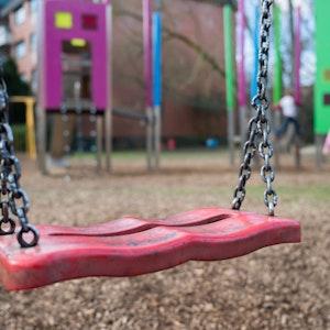 Eine Schaukel hängt auf einem Kinderspielplatz.