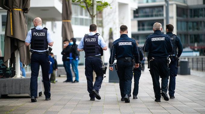 Sechs Mitarbeiter des Ordnungsamtes und Polizisten gehen an der Promenade am Phönixsee entlang.