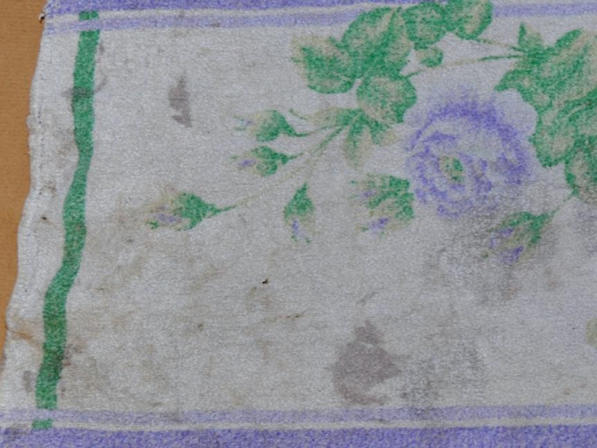 Das verschmutzte Handtuch hat ein Blumenmuster mit grüner sowie lilafarbener Umrandung.