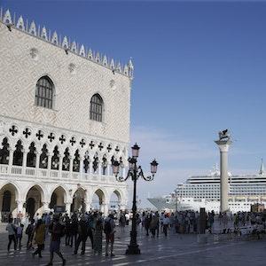 Ein Kreuzfahrtschiff fährt im Sommer 2019 am Markusplatz in Venedig vorbei, auf dem Platz stehen zahlreiche Menschen, die Sonne scheint. Italiens Regierung hat ein Durchfahrtsverbot für große Kreuzfahrtschiffe durch einen Teil der Lagune von Venedig beschlossen.