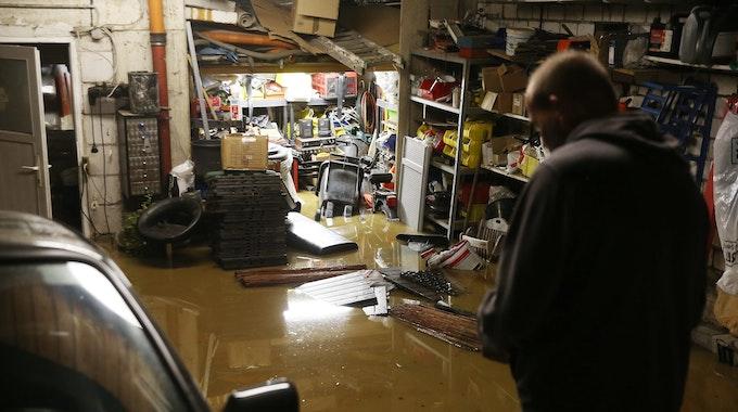 Ein Hausbesitzer steht in seiner überfluteten Garage, Regale stehen unter Wasser, ein Auto steht neben ihm.