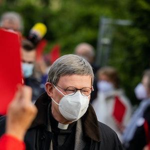 Kardinal Rainer Maria Woelki, Erzbischof von Köln, geht durch einen Spalier aus Gemeindemitgliedern, die ihm die Rote Karte zeigen.