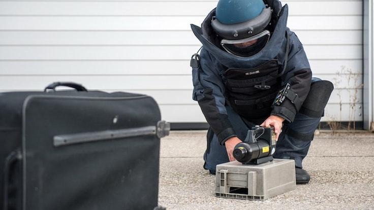 Ein Entschärfer in Schutzanzug untersucht mit Spezialgerät einen herrenlosen Koffer.