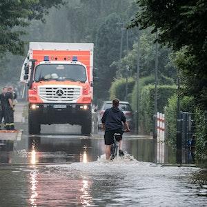 Ein Fahrradfahrer fährt am 14. Juli 2021 durch eine überflutete Straße in der Düsseldorfer Ostparksiedlung. Im Hintergrund steht ein Einsatzfahrzeug der Rettungskräfte.