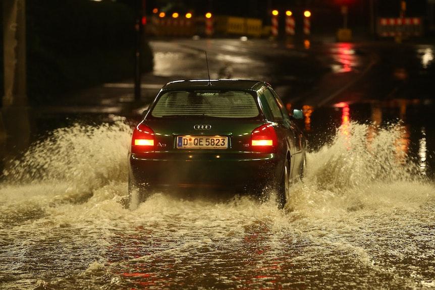 Ein PKW fährt durch eine nach Starkregen überflutete Bahnunterführung.