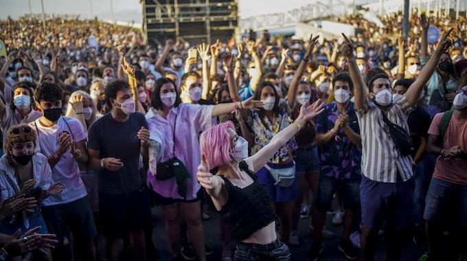 Menschen mit Mund-Nasen-Schutz besuchen das Cruilla Musikfestival in Barcelona und feiern.