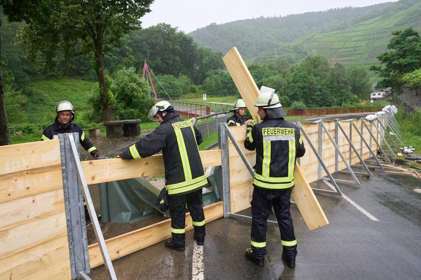 Feuerwehrleute errichten auf einer Straße eine Sperrwand aus Holz.